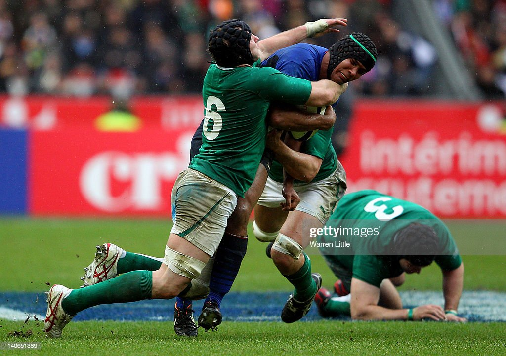 French Captain, Thierry Dusautoir is tackled by Stephen Ferris and Donncha O'Callaghan of Ireland during the RBS Six Nations match between France and Ireland at Stade de France on March 4, 2012 in Paris, France.