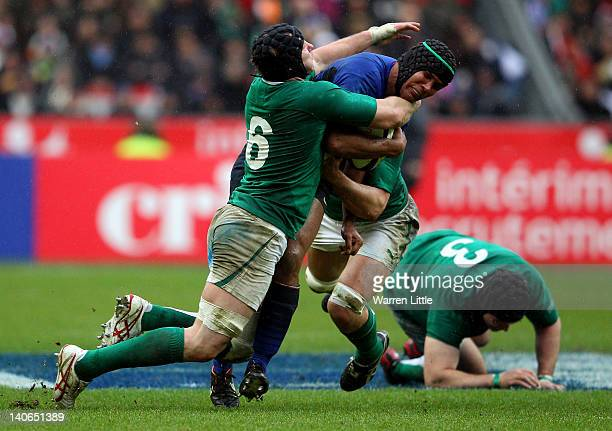 French Captain Thierry Dusautoir is tackled by Stephen Ferris and Donncha O'Callaghan of Ireland during the RBS Six Nations match between France and...