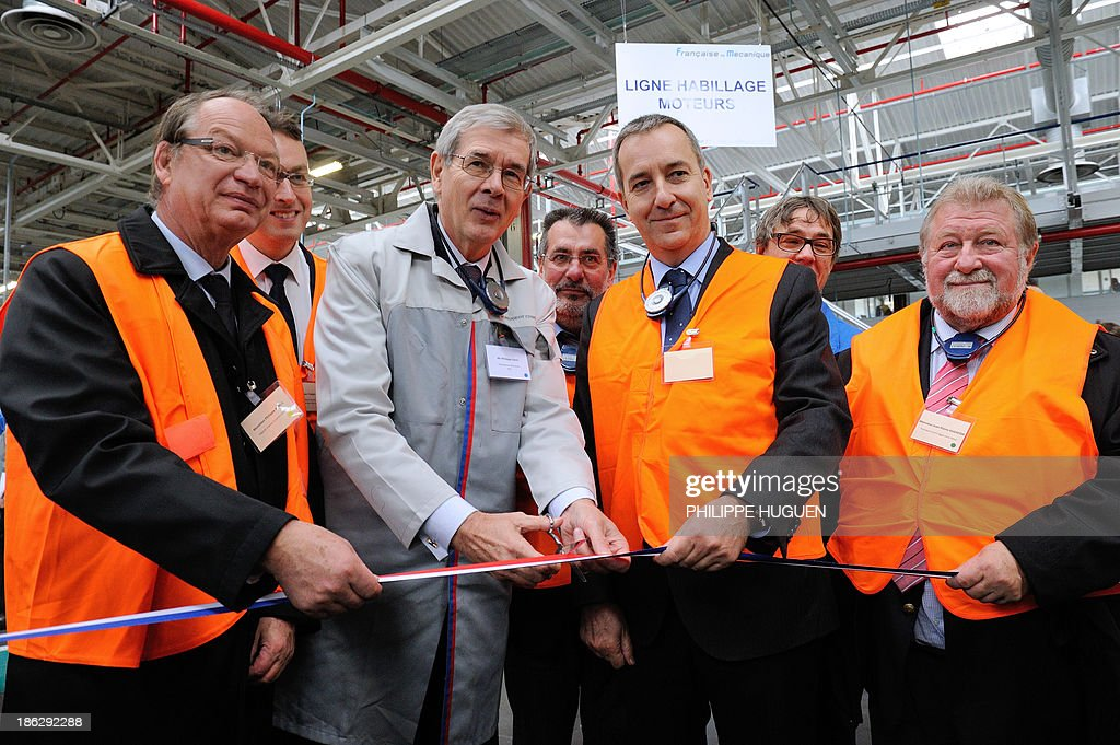 French carmaker PSA Peugeot Citroen Chairman Philippe Varin (C) cuts a ribbon alongside socialist deputy Philippe Kemel (L), the Prefect of the Pas-de-Calais French department Denis Robin (2ndR) and former socialist deputy-mayor of Lievin Jean-Pierre Kucheida (R) during the inauguration of an assembly line for the production of PSA's new car engine, the three-cylinder 'EB Turbo Pure Tech', on October 29, 2013 at the Francaise de Mecanique plant in Douvrin.