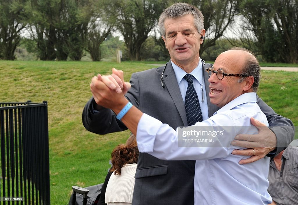 French centrist party Modem deputy Jean Lassalle (L) dances with a militant as he attends his party's meeting in Guidel, western France, on September 29, 2013. Modem's president Francois Bayrou said on September 29 that French President Francois Hollande hadn't achieved his 'promises' and praised German chancellor Angela Markel's 'courage'.