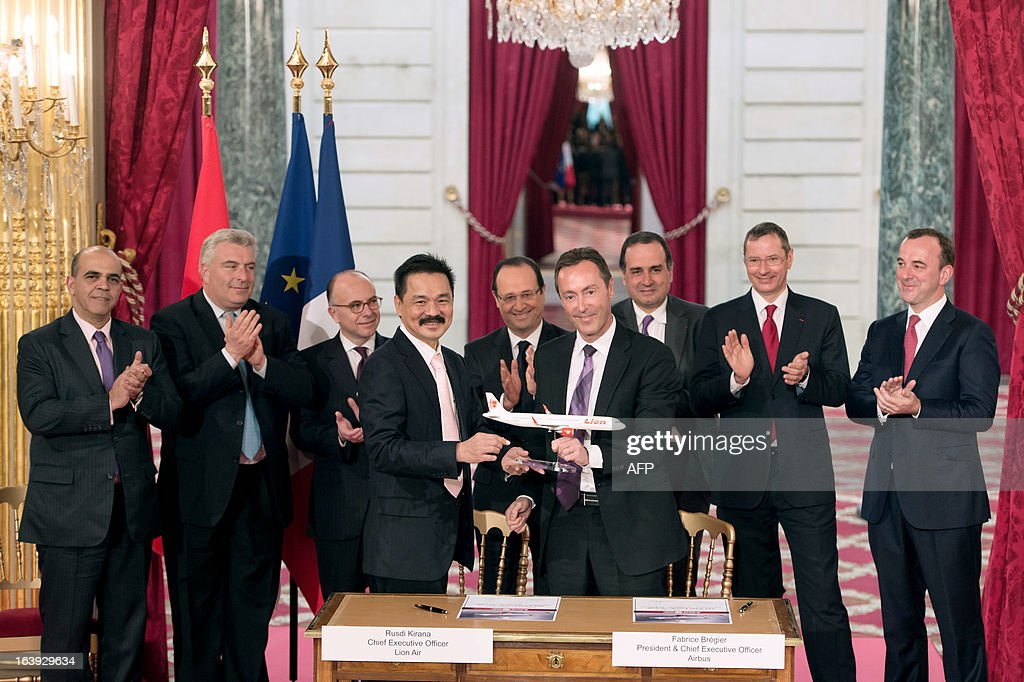 French CEO of European aerospace giant Airbus Fabrice Bregier (C, right) and Lion Air founder and president director Rusdi Kirana (C, left) are applauded by France's President Francois Hollande (C, background), after signing a contract during a ceremony at the Elysee presidential palace in Paris on March 18, 2013. Airbus announced a record order worth 18.4 billion euros ($ 23.8 billion) from Indonesia's Lion Air for 234 medium-haul A320 jets. Lion Air, Indonesia's largest private carrier and one of the world's fastest growing airlines, is a new client for Airbus as it has previously been equipped almost exclusively by US rival Boeing. LANGLOIS