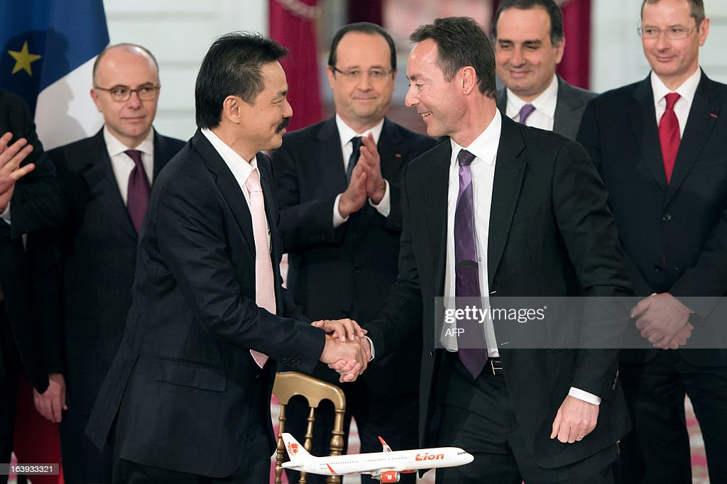 French CEO of European aerospace giant Airbus Fabrice Bregier (C, right) shakes hands with Lion Air founder and president director Rusdi Kirana (C, left) as France's President Francois Hollande (C, background) applauds, after signing a contract during a ceremony at the Elysee presidential palace in Paris on March 18, 2013. Airbus announced a record order worth 18.4 billion euros ($ 23.8 billion) from Indonesia's Lion Air for 234 medium-haul A320 jets. Lion Air, Indonesia's largest private carrier and one of the world's fastest growing airlines, is a new client for Airbus as it has previously been equipped almost exclusively by US rival Boeing. LANGLOIS