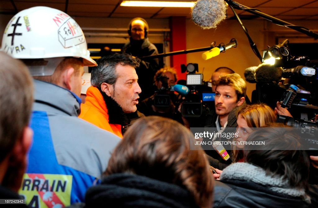 French CFDT union representative Edouard Martin (C) speaks to journalists, surrounded by ArcelorMittal workers, after listening to the speech of French Prime Minister on French TV, on November 30, 2012, in Florange. France asserted that an investor was ready and willing to put 400 million euros ($515 million) into a steel plant at the centre of a dispute between the owner ArcelorMittal and the government. The Socialist administration has threatened to nationalise the Florange plant in northeastern France if Mittal goes ahead with plans to close permanently two blast furnaces on the site that have been inactive for over a year. VERHAEGEN