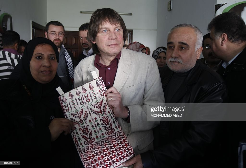 French CGT labour union leader Bernard Thibault (C) receives a Palestinian handmade gift during his visit to Gaza City on February 12, 2013.