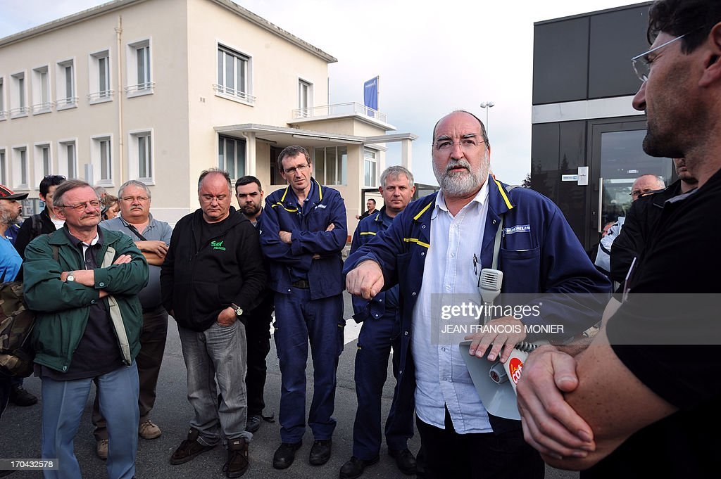 French CGT union delegate Claude Guillon (2ndR) addresses his fellow workers after a briefing organized by the factory management on June 10, 2013 in Joue Les Tours. The French tyre manufacturer announced it would cease the manufacture of truck tyres at the site in the country's west by 2015, slashing 700 jobs due to plummeting demand in Europe, and concentrate production on its factory at La Roche-sur-Yon, also located in western France. That site's annual production would increase from the current level of 800,000 to 1.6 million by 2019, creating around 170 new jobs.