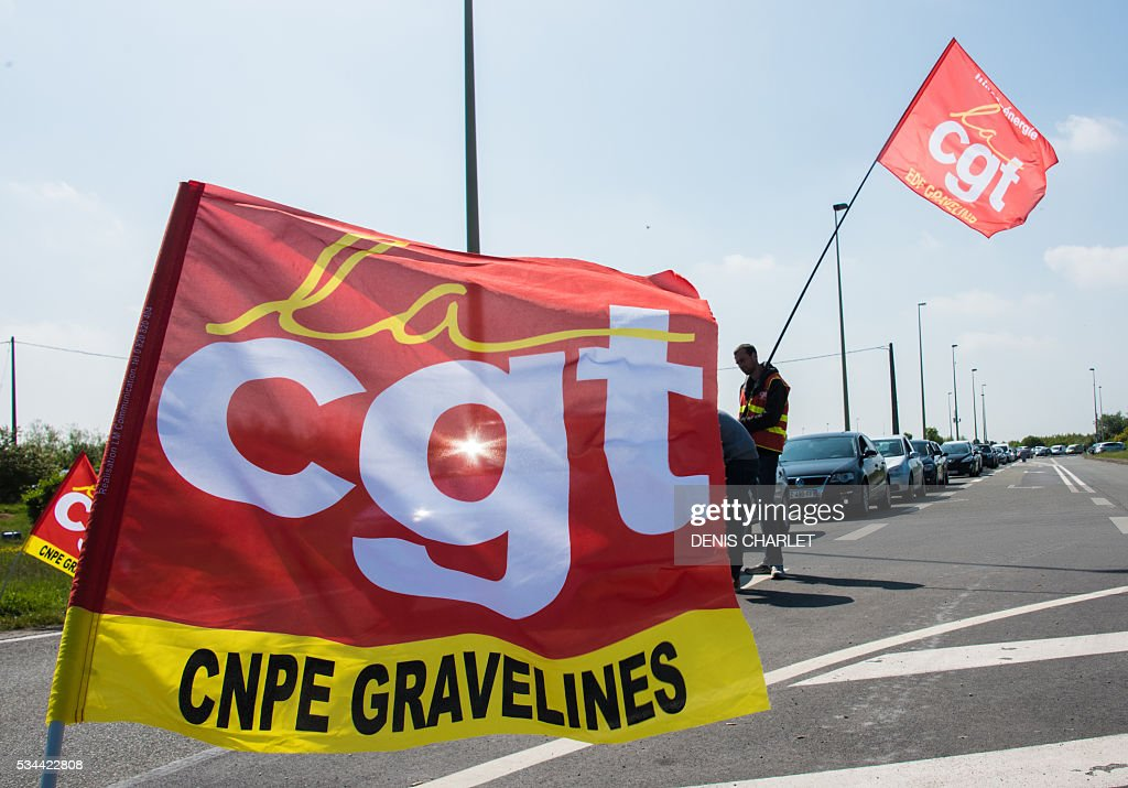 French CGT union members distribute leaflets outside the nuclear power plant at Gravelines, near Dunkirk western France, as the nation's workers strike against the government's labour reform law, on May 26, 2016 Striking French workers disrupted oil refineries and nuclear power stations and halted planes and trains in mounting industrial action against labour market reforms. / AFP / DENIS