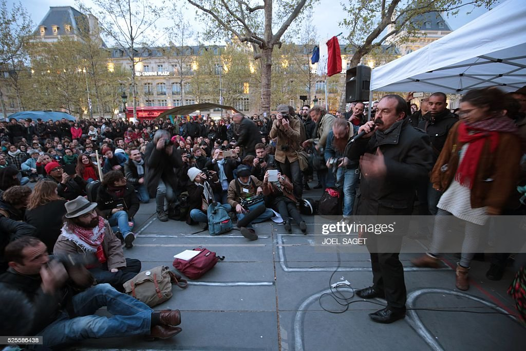 French CGT union Secretary-General Philippe Martinez (R) speaks on the Place de la Republique during the Nuit Debout, or 'Up All Night' movement on April 28, 2016 in Paris. The 'Nuit Debout' demonstrations began on March 31 in opposition to the government's proposed labour reforms. Banners read 'We occupy better than this' and 'Where are you Democracy.