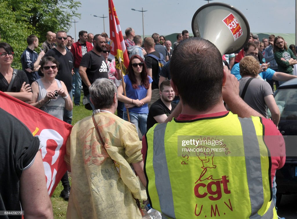 A French CGT union's member speaks in a megaphone as employees block the access of the PSA plant on May 26, 2016 in Valenciennes, northern France during a protest against the government's labour market reforms. The French government's labour market proposals, which are designed to make it easier for companies to hire and fire, have sparked a series of nationwide protests and strikes over the past three months. / AFP / FRANCOIS