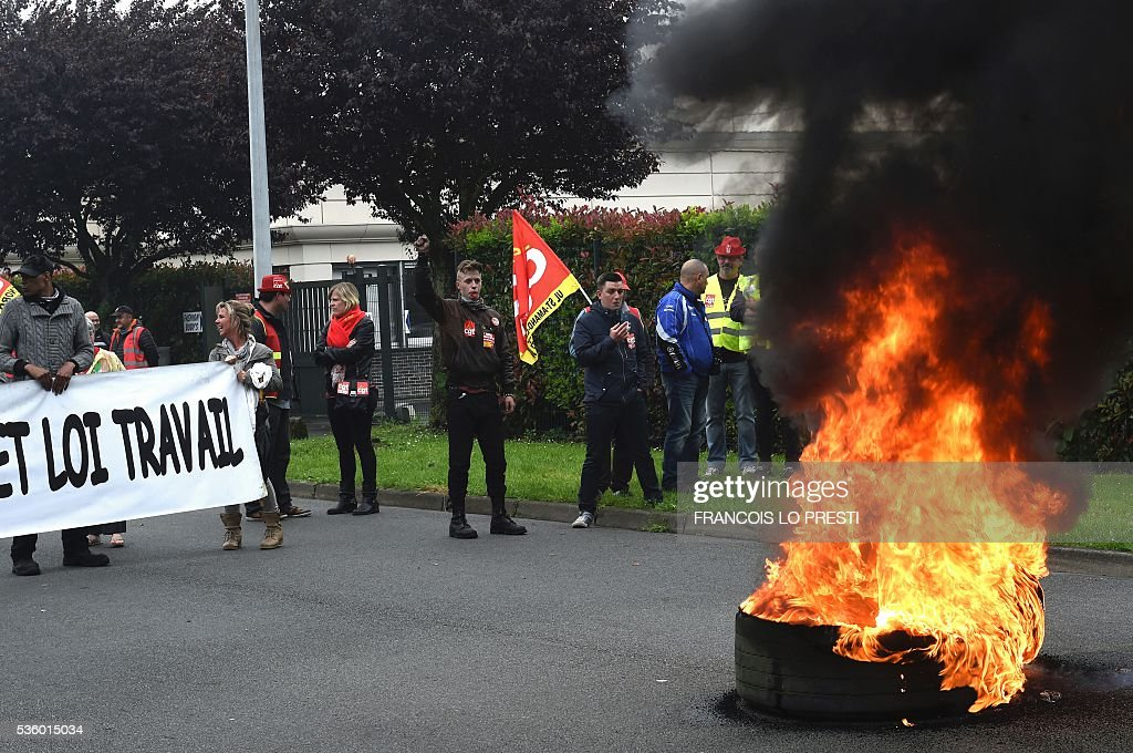 French CGT union's members stand next to tires on fire at the Simmons factory in Saint Amand les Eaux, northern France on May 31, 2016 during a visit of the French Economy Minister after a meeting on reindustrialisation in the North of France. / AFP / FRANCOIS