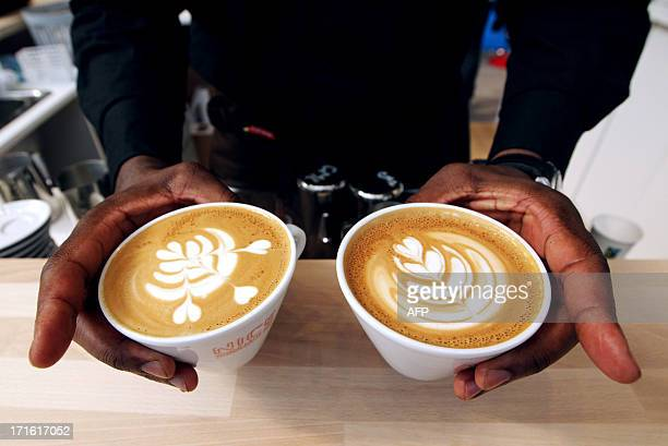French champion of latte art Rudy Dupuy displays his creations during the exhibition 'World of coffee' on June 27 in Nice southeastern France AFP...