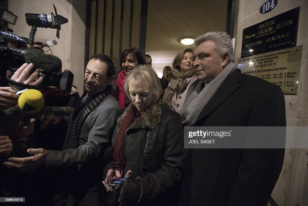 French Charlotte Cassez (C), mother of French national Florence Cassez who was released from prison, flanked by Jean-Luc Romero (L), President of Cassez support comitee, and French minister for Transports and Maritime Economy Frederic Cuvillier (R), Paris' deputy Mayor and socialist party candidate for the 2014 municipal elections, Anne Hidalgo (Back-L) and Partner of French President Francois Hollande, Valery Trierweiler (Back-R), answers journalists questions as she looks at her cell phone on January 23, 2013 in Paris. Mexico's Court announced the immediat relax of Florence Cassez.