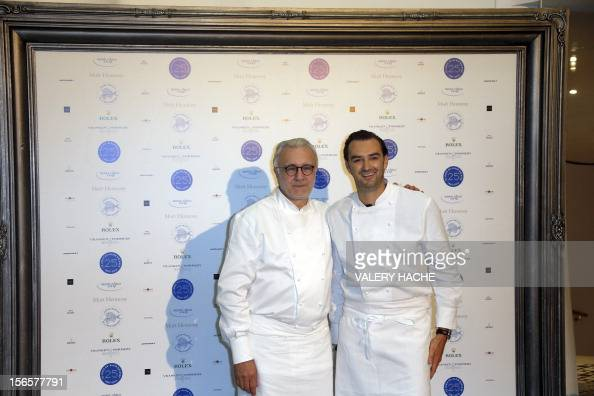 French chef Alain Ducasse poses with French chef Cyril Lignac as part of the festivities marking the 25th anniversary of his restaurant 'Le Louis XV'...