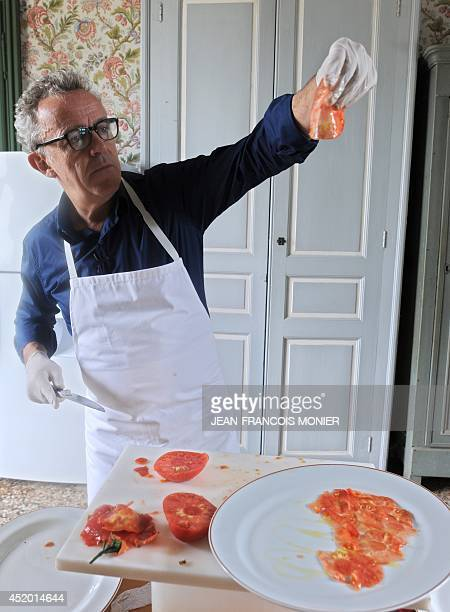 French chef Alain Passard prepares a tomato carpaccio with seasonal tomatoes he just picked from his vegetable garden in FillesurSarthe western...