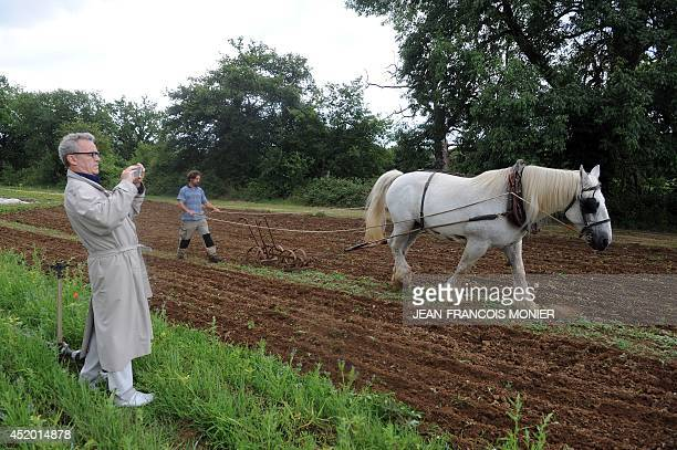 French chef Alain Passard takes a photo as an aide conducts a horse to plow the soil of Passard's vegetable garden in FillesurSarthe western France...
