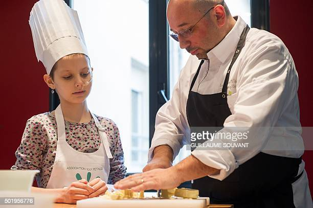 French chef Guillaume Dallay teaches a girl suffering from leukemia to cook at the Clocheville hospital in Tours central France on December 7 2015...
