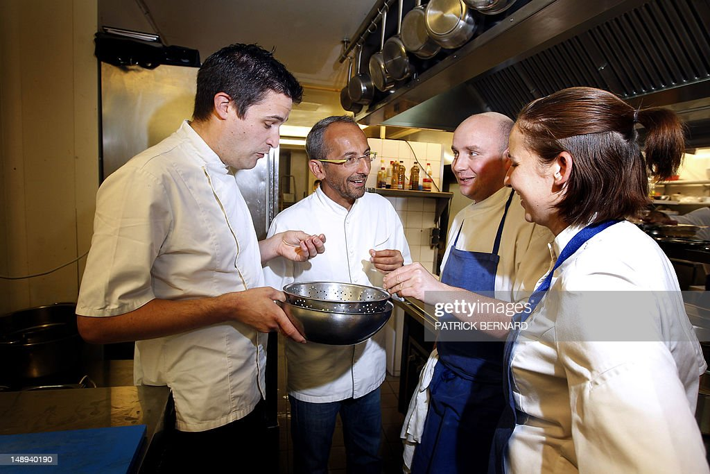 French Chef, Michel Portos (C), Best Cook Award 2012 and two-star ranking in the Michelin gastronomy guide, poses with his cooks on July 16, 2012 in his restaurant, The Saint-James, in Bouillac, near Bordeaux, southwestern France. Portos will move at the end of the year to his hometown in Marseille, southern France. AFP PHOTO / PATRICK BERNARD