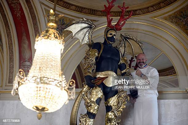 French chef Philippe Etchebest poses with a statue dressed as devil in his new restaurant called 'The Fourth wall' under the arches of the great...
