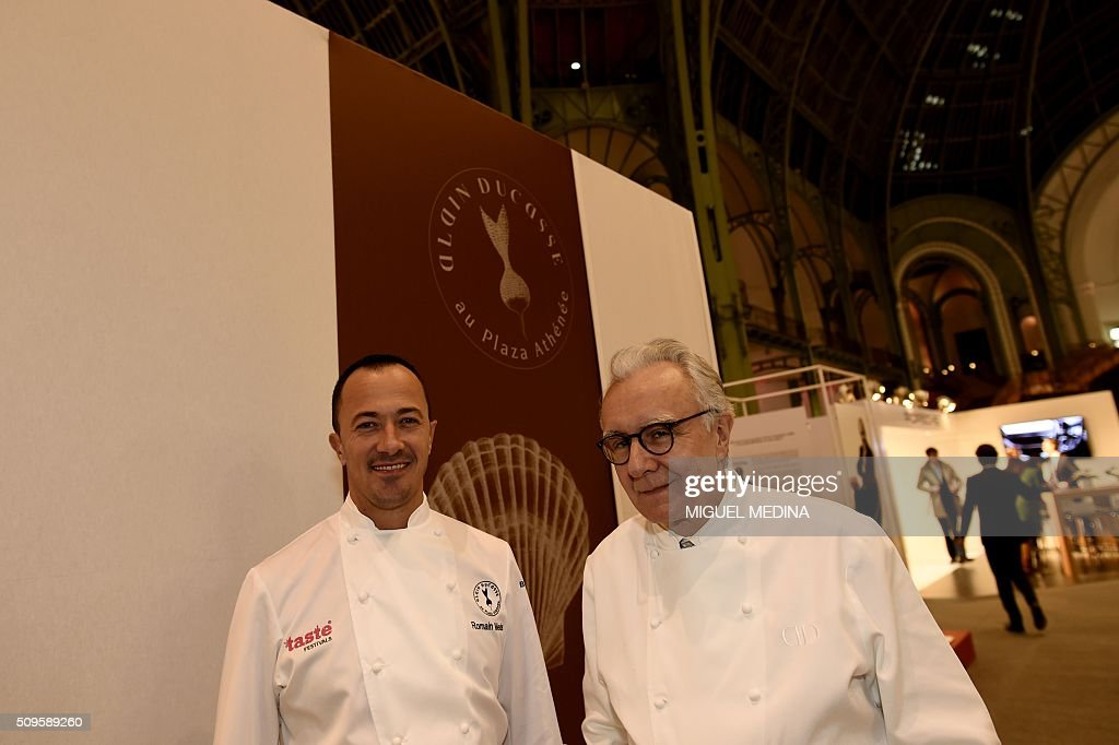 French chef Romain Meder (L) and renowned french chef Alain Ducasse pose for photographs during the Taste of Paris, Festival of Chefs, at the Grand Palais in Paris on February 11, 2016. / AFP / MIGUEL MEDINA