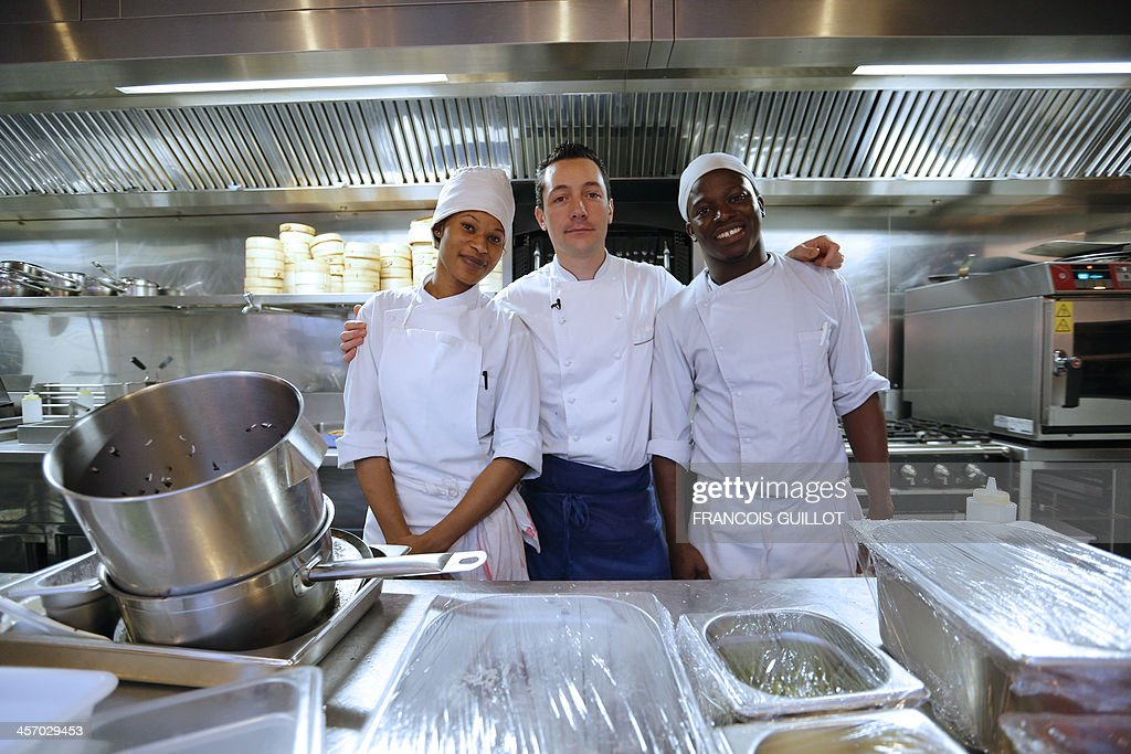 TAIX - French chef William Pradeleix (C) pose with his two apprentice cook Moussa Coulibaly (R) and Djetinin Doumouya on December 12, 2013 in his Paris' restaurant 'Manger.'