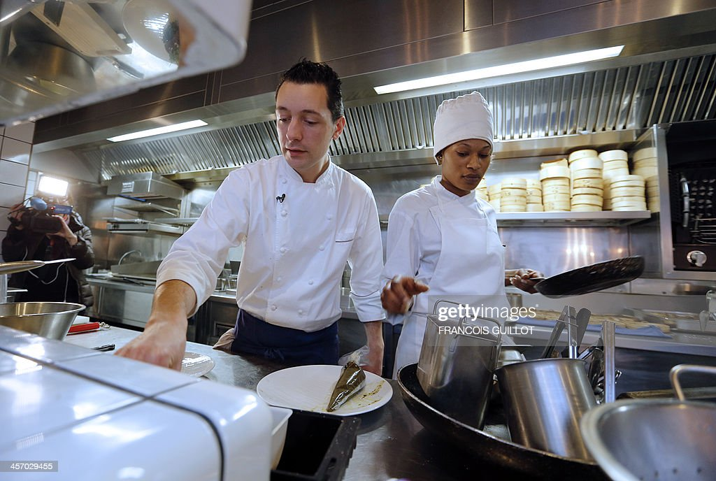 TAIX - French chef William Pradeleix (L) works with one of his apprentice cook Djetinin Doumouya on December 12, 2013 in his Paris' restaurant 'Manger.' AFP PHOTO / FRANCOIS GUILLOT