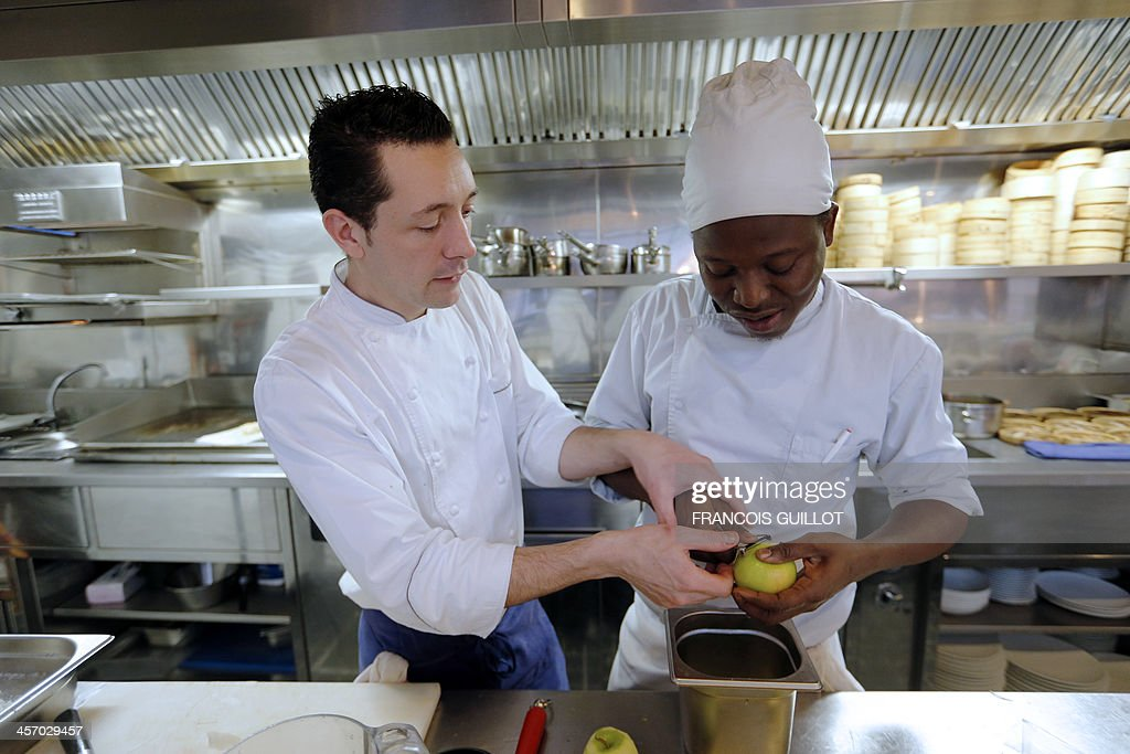 TAIX - French chef William Pradeleix (L) works with one of his apprentice cook Moussa Coulibaly on December 12, 2013 in his Paris' restaurant 'Manger.' AFP PHOTO / FRANCOIS GUILLOT