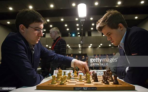 French chess player Maxime VachierLagrave moves a piece on the board during his match against Norwegian chess player and current World Chess Champion...