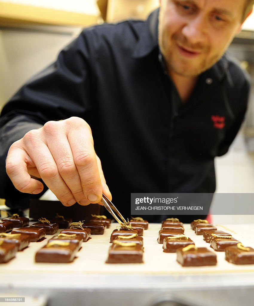 French chocolate maker Sylvain Musquar uses tweezers to place gold-coated crickets on chocolates on October 12, 2013 in his store in Villers-les-Nancy, northeastern France. After working in Japan and South Korea, Musquar had the idea of placing gold-coated mealworms or crickets on his chocolates.