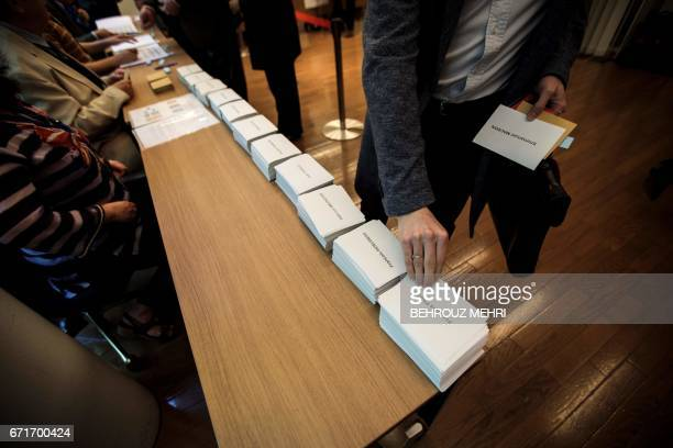 A French citizen picks ballot papers marked with the names of presidential candidates to vote in the first round of the country's presidential...