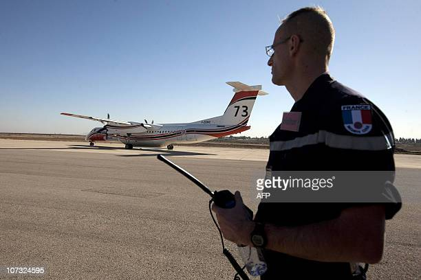 A French civil security member stands near a Dash 8 waterbomber plane that arrived from France to Ramat David air base in Israel on December 4 2010...