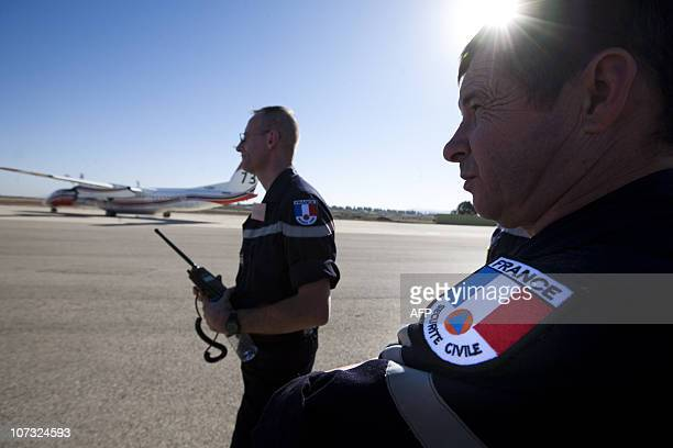French civil security members stand near a Dash 8 waterbomber plane that arrived from France to Ramat David air base in Israel on December 4 2010 in...