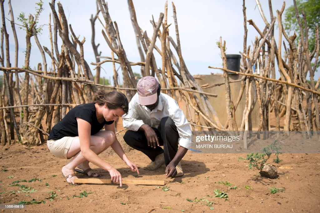 French CNRS researcher Chloe Guerbois (L) measures an elephant footprint with Victor Bitu (R), the owner of a field destroyed by elephants, on November 19, 2012 in the village of Magoli, at the border of Hwange National Park in Zimbabwe. AFP PHOTO MARTIN BUREAU