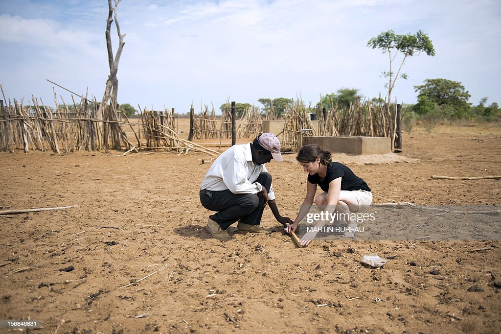 French CNRS researcher Chloe Guerbois (R) measures an elephant footprint with Victor Bitu (L), the owner of a field destroyed by elephants, on November 19, 2012 in the village of Magoli, at the border of Hwange National Park in Zimbabwe.