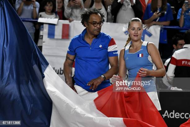 French coach Yannick Noah and French player French player Kristina Mladenovic celebrate with a French flag after she wins her game Spanish player...