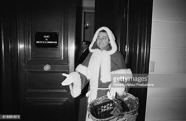 French comedian Coluche dressed in a Santa Claus outfit visits the offices of the French Ministry of Communication He is bringing them 50000...