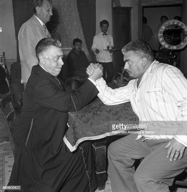 French comedian Fernandel as Don Camillo arm wrestling with Gino Cervi as Peppone on the set of the film 'Don Camillo Monsignor' the fourth episode...