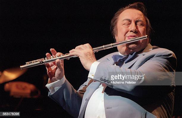 French comedian Raymond Devos plays the flute during a live performance in Brussels