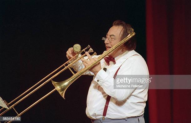 French comedian Raymond Devos plays the trombone during a live performance in Brussels