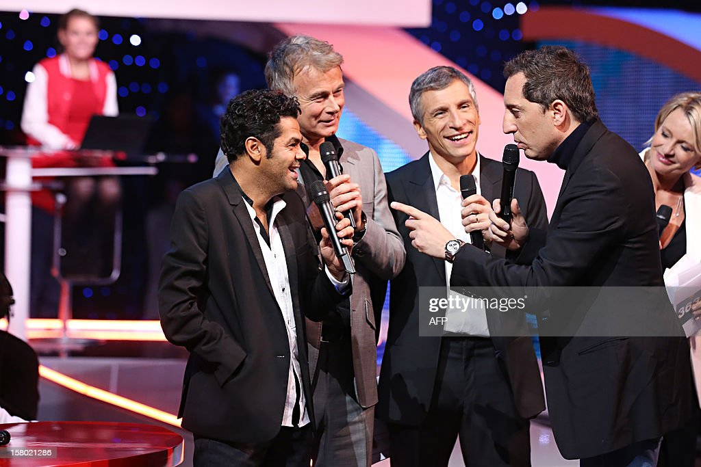 French comic and godfather of the 2012 Telethon's edition, Franck Dubosc (2L), French TV host Nagui (2R), French comics Jamel Debbouze (L) and Gad Elmaleh (R) chat during the 26th Telethon, France's biggest annual fund-raising event during 30 hours of live television transmission, on December 8, 2012 in Saint-Denis, north of Paris. The event aims at collecting funds for research on genetic diseases such as myopathy, a neuromuscular disease. This year's edition raised 81,065,239 Euros.