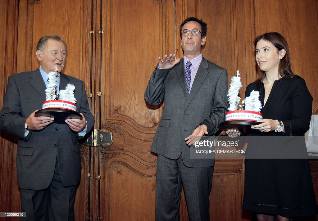French comic book illustrator and scriptwriter Albert Uderzo (L), the 'father' of 'Asterix the Gaul' and Anne Goscinny (R) the daughter of Rene Goscinny who was the co-writer of the comic book series, pose with trophies given by Arnaud Nourry (C) chairman and CEO of Hachette Livre book group, to mark the 350 millionth copy of the 34 Asterix books sold worldwide, at the Hachette headquarters in Paris on September 26, 2011.