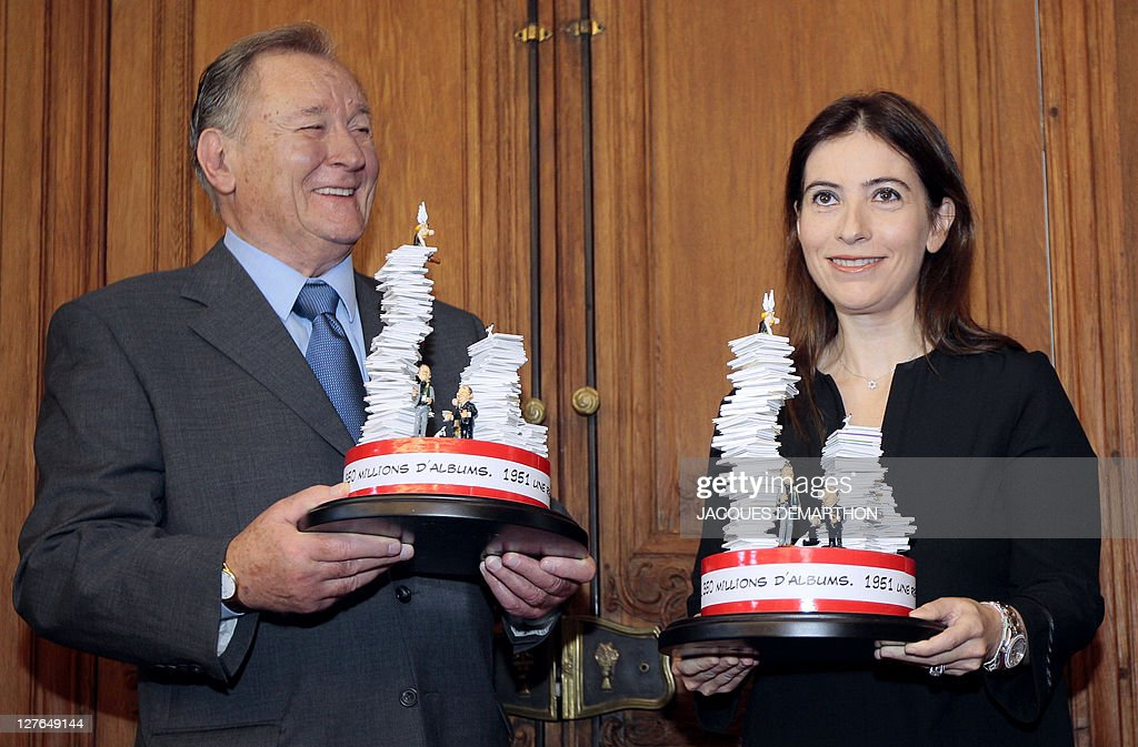 French comic book illustrator and scriptwriter Albert Uderzo (L), the 'father' of 'Asterix the Gaul' and Anne Goscinny (R) the daughter of Rene Goscinny who was the co-writer of the comic book series, pose with trophies to mark the 350 millionth copy of the 34 Asterix books that have been sold worldwide, at the French book group Hachette headquarters in Paris on September 26, 2011.