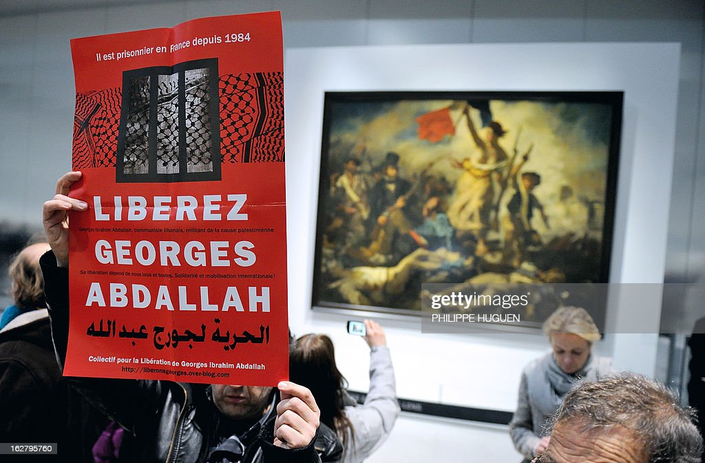 French communist militants hold a placard reading 'Free Georges Abdallah' on February 27, 2013 as they are gathered in front of French painter Eugene Delacroix' masterpiece 'La Liberté guidant le Peuple' (Liberty leading the people) at the Louvre-Lens Museum in Lens, northern France, during a protest demanding the release of a pro-Palestinian Lebanese militant Georges Ibrahim Abdallah who has spent 28 years in French jails. Abdallah, a former militiaman in the Popular Front for the Liberation of Palestine (PFLP) who has spent 28 years in French jails, was granted parole on November 21, 2012 but remained behind bars following an appeal by the state. Paris sentence enforcement court will judge on February 28, 2013 the prosecution's appeal upon the judges' rule to postpone their final decision. AFP PHOTO PHILIPPE HUGUEN