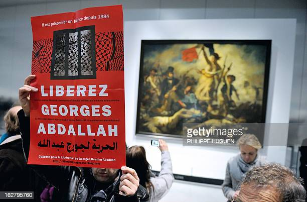 French communist militants hold a placard reading 'Free Georges Abdallah' on February 27 2013 as they are gathered in front of French painter Eugene...