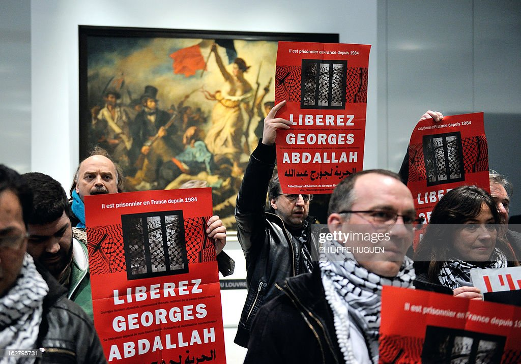 French communist militants hold placards reading 'Free Georges Abdallah' on February 27, 2013 as they are gathered in front of French painter Eugene Delacroix' masterpiece 'La Liberté guidant le Peuple' (Liberty leading the people) at the Louvre-Lens Museum in Lens, northern France, during a protest demanding the release of a pro-Palestinian Lebanese militant Georges Ibrahim Abdallah who has spent 28 years in French jails. Abdallah, a former militiaman in the Popular Front for the Liberation of Palestine (PFLP) who has spent 28 years in French jails, was granted parole on November 21, 2012 but remained behind bars following an appeal by the state. Paris sentence enforcement court will judge on February 28, 2013 the prosecution's appeal upon the judges' rule to postpone their final decision.
