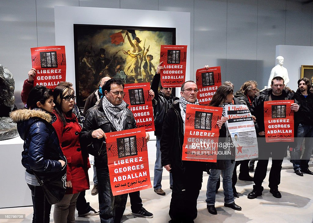 French communist militants hold placards reading 'Free Georges Abdallah' on February 27, 2013 as they are gathered in front of French painter Eugene Delacroix' masterpiece 'La Liberté guidant le Peuple' (Liberty leading the people) at the Louvre-Lens Museum in Lens, northern France, during a protest demanding the release of a pro-Palestinian Lebanese militant Georges Ibrahim Abdallah who has spent 28 years in French jails. Abdallah, a former militiaman in the Popular Front for the Liberation of Palestine (PFLP) who has spent 28 years in French jails, was granted parole on November 21, 2012 but remained behind bars following an appeal by the state. Paris sentence enforcement court will judge on February 28, 2013 the prosecution's appeal upon the judges' rule to postpone their final decision. AFP PHOTO PHILIPPE HUGUEN