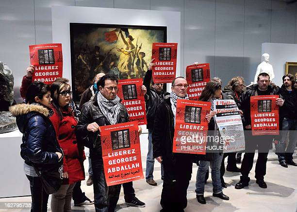 French communist militants hold placards reading 'Free Georges Abdallah' on February 27 2013 as they are gathered in front of French painter Eugene...
