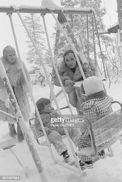 French composer Charles Aznavour stands with his wife Ulla as she pushes their two children on a swing set at their home in Crans Switzerland