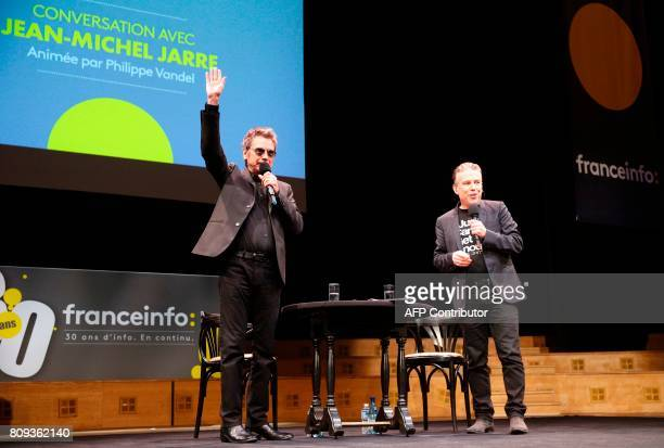French composer performer and record producer JeanMichel Jarre waves at the audience as he is flanked by French journalist Philippe Vandel on stage...