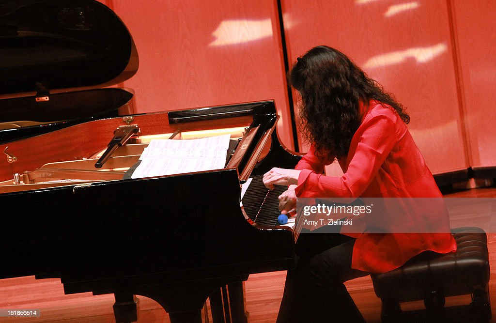 French concert pianist Marielle Labeque uses a percussion instrument as she performs with her sister Katia Labeque and the Kalakan Trio on percussion Ravel's 'Bolero' arrangement for duo piano as part of 'Imagine' family concerts programming at the Queen Elizabeth Hall on February 17, 2013 in London, England.