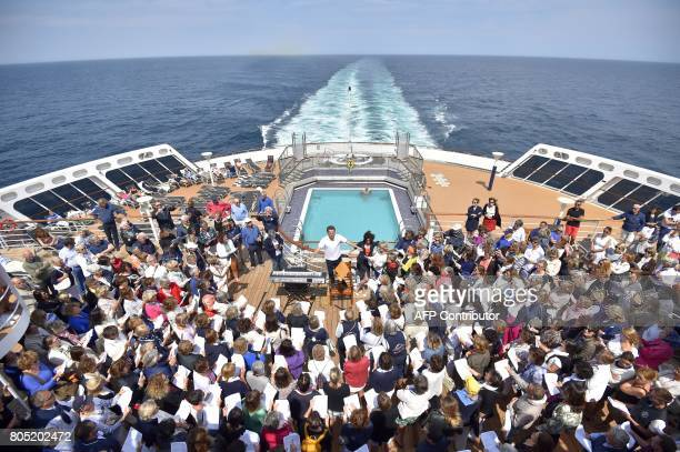 French conductor and violinist JeanChristophe Spinosi leads the rehearsal of a chorale of passengers on June 29 2017 aboard the Cunard cruise liner...