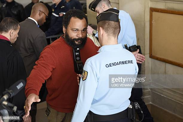 French controversial comic Dieudonne M'bala M'bala is checked by French gendarmes as he arrives at the Paris courthouse on March 12 for the trial of...